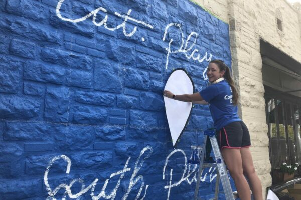 South Plaza Mural - Ruthie stenciling in the heart